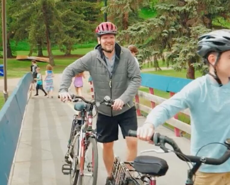 Dr. Mark Knoefel alongside his bicycle and family